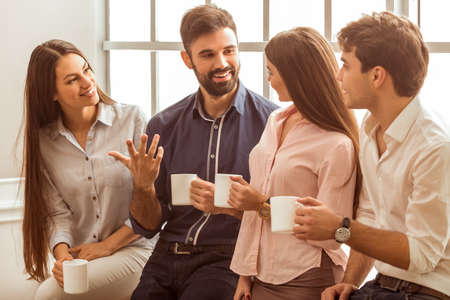 office break: Coffee break chat. Group of attractive business people, standing next to each other, holding a cups, smiling standing at the window