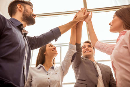 team hands: Group of young business people giving a palm up standing with their arms raised in the air to indicate their success and approval