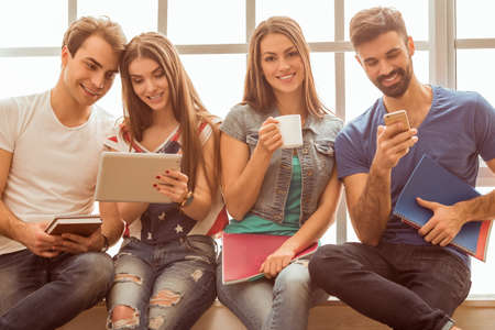 cup four: Four young attractive people, keeping at hand tablet computer, cup, smartphone and notebook, sit on the windowsill, smiling Stock Photo
