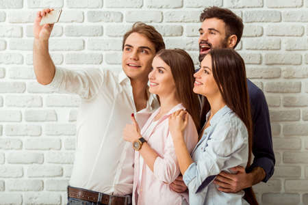smiling faces: Capturing the moment. Top view of four cheerful young people bonding to each other and making selfie on smart phone while standing against a background of brick wall