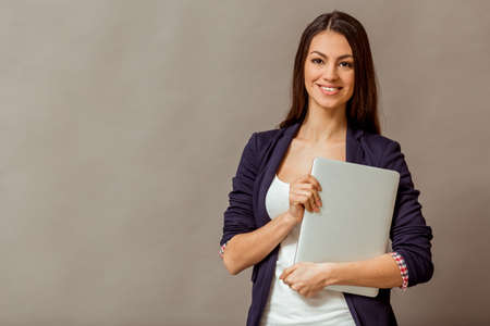 keeps: Beautiful young business woman with long hair, keeps laptop in hand, smiling, looking at camera, on a gray background Stock Photo