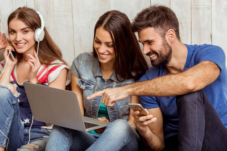 Group of attractive young people sitting on the floor using a laptop, Tablet PC, smart phones, headphones listening to music, smiling