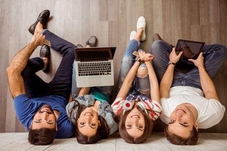 Groep van aantrekkelijke jonge mensen zitten op de vloer met behulp van een laptop, tablet-pc's, smartphones, een koptelefoon luisteren naar muziek, glimlachend