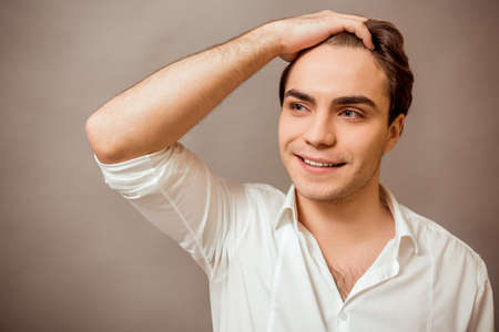 keep an eye on: Portrait of a young man in a white shirt, keeps one arm behind his head, smiling, on a gray background