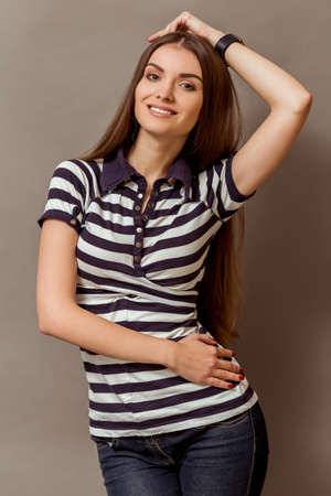 light hair: Young beautiful girl with long brown hair posing in studio, smiling, looking into the camera, on a gray background Stock Photo