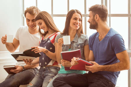 cup four: Four young attractive people sitting on the window sill, smiling, keeping in hands cup and notebook