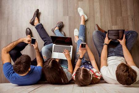 jeune fille adolescente: Groupe de jolies jeunes gens assis sur le sol en utilisant un ordinateur portable, Tablet PC, les téléphones intelligents, un casque d'écoute de la musique, sourire Banque d'images