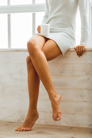 naked legs: Girl hold in hands a cup sitting on a window-sill at home. Smooth legs African American women close Stock Photo