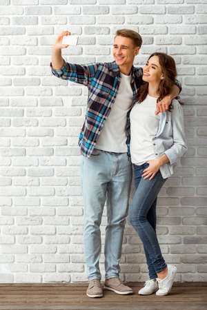 taking a wife: Happy young couple makes selfie, dressed in stylish clothes on brick wall background Stock Photo