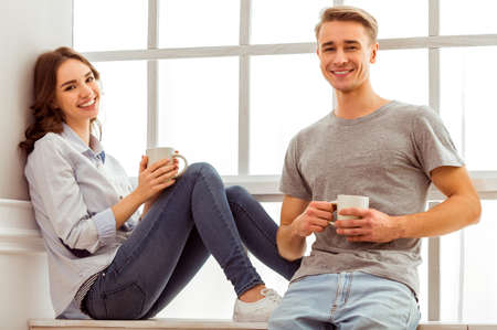 people looking: Young happy couple sitting on the windowsill, holding a cup in hand at home Stock Photo