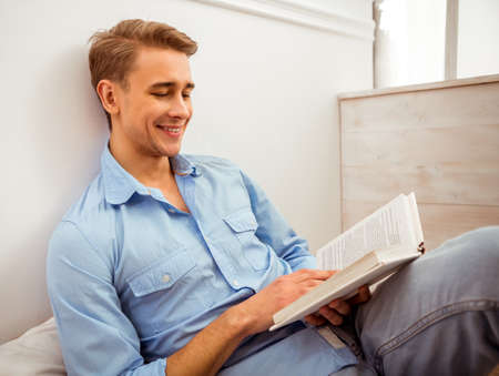 cushioned: Young handsome man in the blue shirt and jeans reading a book, sitting on the floor on pillows at home