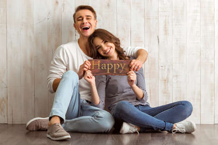 home keeping: Happy young couple keeping the sign that says, sitting on the floor Wooden at home