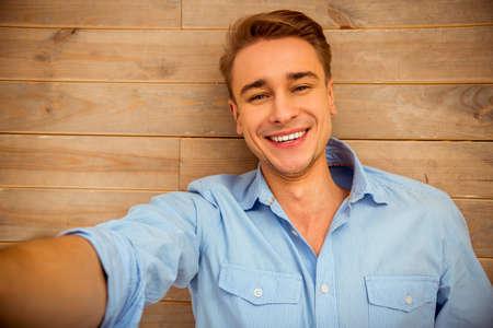 Junger stattlicher Mann im blauen T-Shirt, auf dem hölzernen Boden liegend, lächelnd, die Bilder von sich selbst. Nahansicht