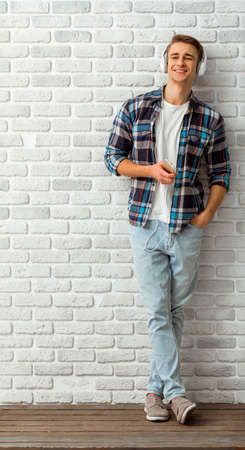 Giovane uomo bello vestito con abiti alla moda, ascoltare la musica con le cuffie sul cellulare, contro un muro di mattoni