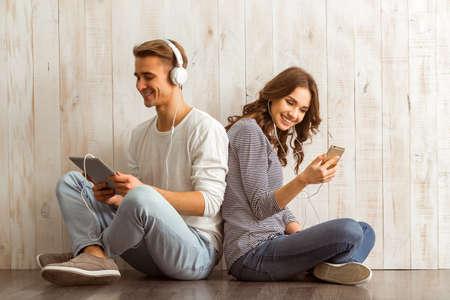 Meisje met behulp van smartphone, en de man met behulp van een tablet met een koptelefoon luisteren naar muziek en leunend op elkaar zitten op een houten vloer thuis