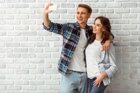 taking a wife: Happy young couple makes selfie, dressed in stylish clothes on brick wall background. Close-up