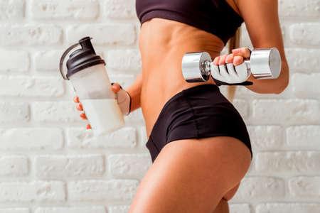 Körper der schönen Sportlerin in Sporthandschuhe Hantel und Shaker mit Sporternährung, stehend gegen weiße Mauer, close-up