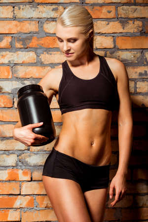 a jar stand: Beautiful blonde sportswoman looking down and holding a jar of protein, standing against brick wall Stock Photo