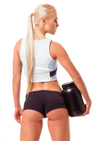 a jar stand: Back view of beautiful blonde sportswoman holding a jar of protein, isolated on white background