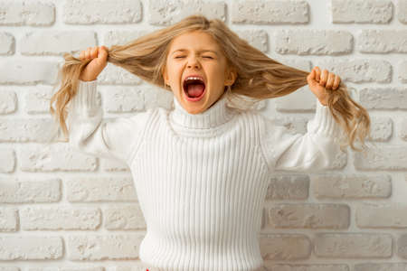 Portrait of a pretty little blonde girl showing emotions, screaming and pulling her hair while standing against white brick wall