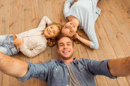Top view of beautiful young family looking in camera and smiling while lying on wooden floor at home. Father making selfie.