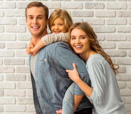 Beautiful young family hugging, looking in camera and smiling while standing against white brick wall