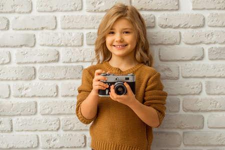 jolie petite fille: Portrait d'une jolie petite fille blonde souriante et tenant un appareil photo en position debout contre le mur de briques blanches Banque d'images