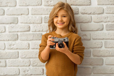 Portrait of a pretty little blonde girl smiling and holding a camera while standing against white brick wall