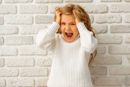 fashion girl style: Portrait of a pretty little blonde girl showing emotions, screaming and pulling her hair  while standing against white brick wall