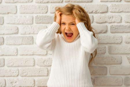 ni�as peque�as: Retrato de una ni�a bonita rubia mostrando emociones, gritando y tirando de su cabello mientras est� de pie contra la pared de ladrillo blanco