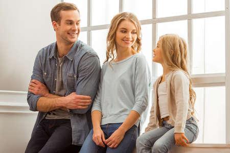niños rubios: jóvenes hermosas padres que escuchan a su hija bastante poco y sonriendo mientras está sentado cerca de la ventana en el país