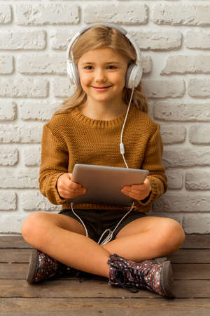 sincere girl: Pretty little blonde girl listening to music and using tablet while sitting cross-legged against white brick wall
