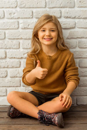 Pretty little blonde girl looking in camera, smiling and showing OK sign while sitting cross-legged against white brick wall