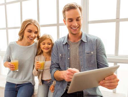 colegiala: padre joven hermosa que usa la tableta y sonriendo mientras est� sentado cerca de la ventana en el pa�s. Una bonita hija y su madre con un vaso de jugo y mirando a la tableta Foto de archivo