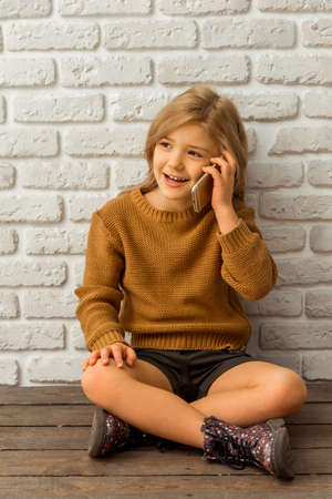 sincere girl: Pretty little blonde girl talking on the phone while sitting cross-legged against white brick wall