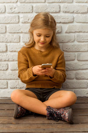 sincere girl: Pretty little blonde girl using smartphone while sitting cross-legged against white brick wall Stock Photo
