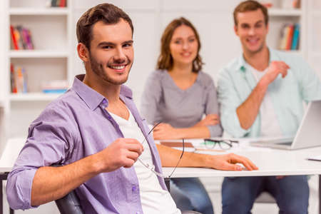 three shelves: Young attractive businessman in casual clothes holding eyeglasses, smiling and looking in camera, in the background people working in office Stock Photo