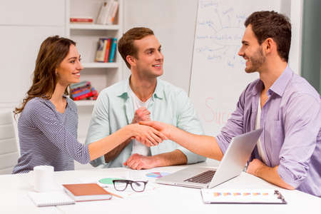 casual business man: Young attractive businessman in casual clothes and beautiful businesswoman shaking their hands and smiling while working in office. Another attractive businessman smiling and supporting.