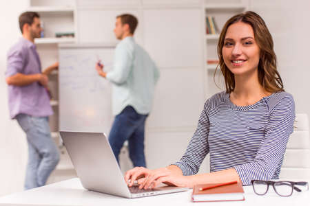 three shelves: Young attractive businesswoman in casual clothes smiling and looking in camera while working in office, in the background men talking