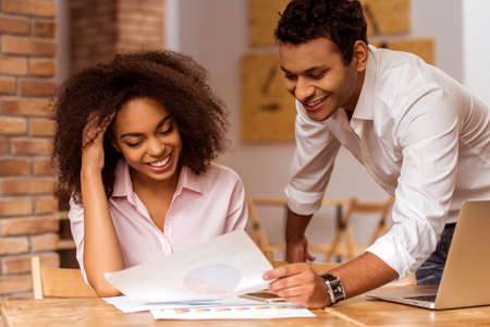 Young attractive Afro-American business couple using laptop, holding graphs and smiling while working in cafe Stock Photo
