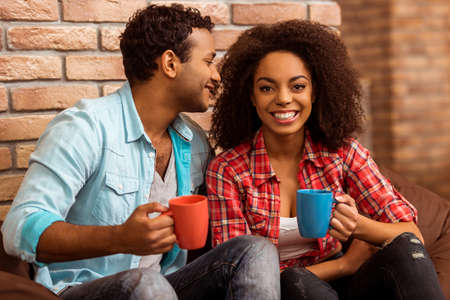 Attractive Afro-American couple drinking coffee, talking and laughing while sitting on chair against brick wall
