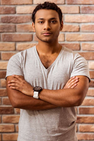 cross armed: Portrait of young handsome Afro-American man looking in camera while standing cross-armed against brick wall