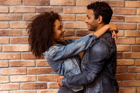 couple: Side view of young attractive Afro-American couple hugging, looking in camera and smiling while standing against brick wall Stock Photo