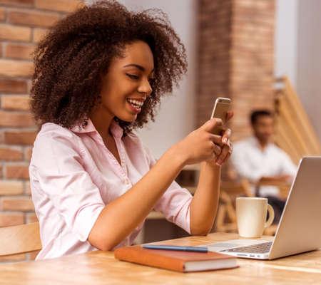 niñas bonitas: bella mujer de negocios teléfono inteligente afroamericana joven y sonriente mientras se trabaja en el café