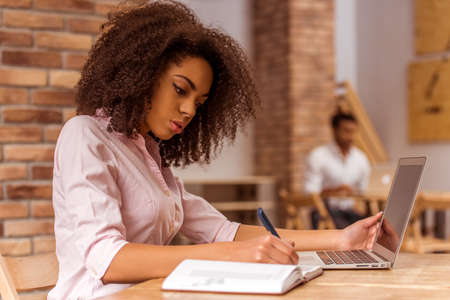 Young beautiful Afro-American businesswoman using laptop and writing in notebook while studying in cafe Banque d'images