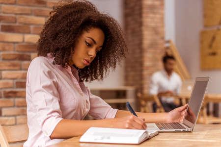 Junge schöne afroamerikanischen geschäftsfrau mit Laptop und schriftlich in Notebook, während im Café studieren Standard-Bild