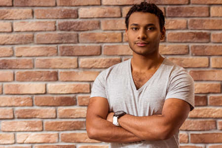 cross armed: Young handsome Afro-American man looking in camera while standing against brick wall Stock Photo