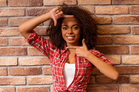 sincere girl: Young beautiful Afro-American woman showing frame, posing and smiling while standing against brick wall Stock Photo