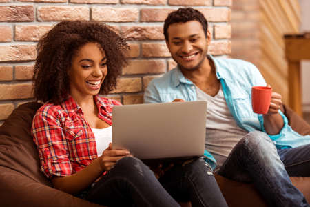 handsome men: Attractive Afro-American couple using laptop, holding a cup and smiling while sitting on beanbag chairs against brick wall