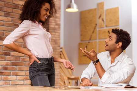 coworker: Young attractive Afro-American business couple talking while working in cafe Stock Photo